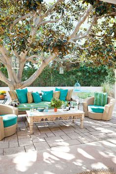 In the outdoor living room of this Malibu ranch by designers Todd Nickey and Amy Kehoe, a vintage sofa and coffee table mix with Janus et Cie chairs.