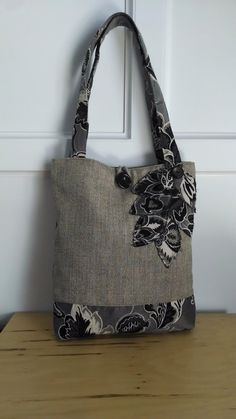 Black, Brown and white tote bag, one of kind from BerkshireCollections. The floral pattern is in the petals, the 26 inch strap handle and along the bottom 4 inches of the this tote bag, front and back. The dripping flower petals are accented with buttons as well as the large button for closure of the tote. This tote measures 15 across and 17 inches in height, fully lined with 3 interior pockets. A bit more sophtisticated in style and yet can be used for everyday. The perfect everything bag.