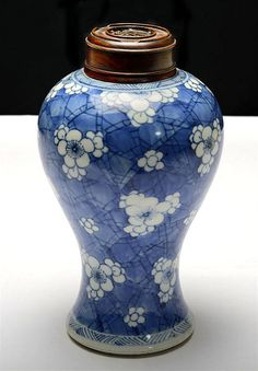 A BLUE AND WHITE VASE QING DYNASTY, KANGXI PERIOD (2) of slender baluster form, painted on the exterior with detached flowerheads reserved on a 'cracked-ice' ground between wave-pattern borders, wood cover  21CM