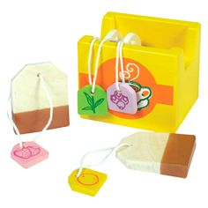 Wooden tea bag set for use in imaginative play. The set includes four different tea bags flavours in a bright yellow box.