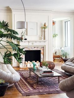 Bohemian-inspired living room with leather clamshell sofas and chairs, a vintage Moroccan area rug and candles in the painted fireplace.