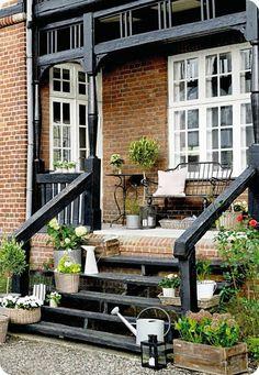 Toves Sammensurium - Wooden steps and railing with brick base behind.