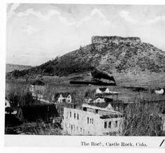 "Castle Rock (the rock formation) from the courthouse on Wilcox Street in town of Castle Rock. Keystone Hotel, City Hotel, Livery Stable, and General Store on Wilcox Street are visible. A train in front of ""the rock"", with smoke coming from the engine, is heading south. Front Street, 5th Street and 4th Street are also visible in 1910. Douglas County History Photograph Collection"