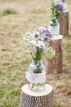 Mason jar lace bouquets site atop tree trunk posts at this country wedding.
