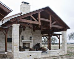 Outdoor living with a fireplace under stunning timber frame trusses.  www.texastimberframes.com https://www.facebook.com/TexasTimberFrames