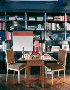 Dine-in Library  Miles Redd designed the ebonized wood and sterling bookshelf, where a colorblock painting by Leora Armstrong hangs. When they're alone, the owners of this Manhattan apartment dine at this carved flip-top game table from Agostino Antiques.