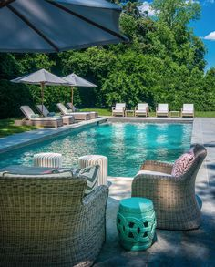 Chic patio features a wicker sofa and chairs adorned with  gray chevron outdoor pillows and pink pillows facing an in ground pool lined with adjustable wicker loungers.
