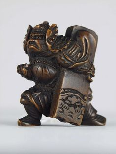 Netsuke featuring a fierce and scowling man wearing winged helmet, striding forward clutching long flat box under left arm. It was a toggle to be attached to the end of a cord and thrust through the sash of a kimono for the support of a purse, pouch or lacquer box. Japan. PAHMA 9-8984.