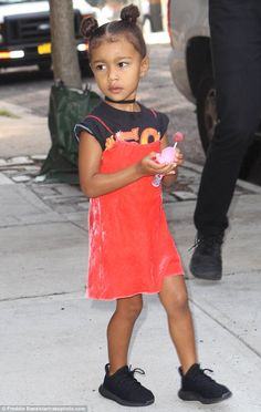 Sugar for the little one: North West held onto a pink lollipop on Saturday as she left the New York residence she has been staying at with mom and dad this summer