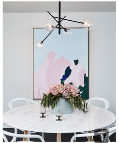 Easy ways to make your dining room pop: add a statement light fixture and a large abstract painting