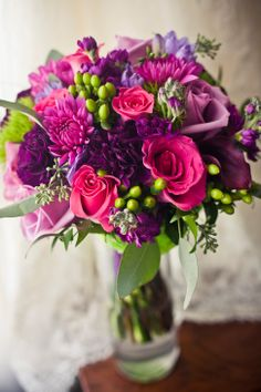 Roses, stock, calla lilies and pops of hypericum berries make a bright, fun bouquet
