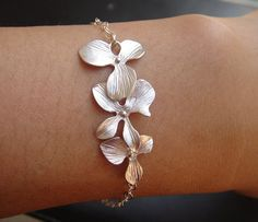 Gorgeous cascade dendrobium orchids of matte white gold plated is wire on to sterling silver chain.closes with sterling silver lobster clasp and freshwater pearl on other end This bracelet is 7.5 inch long. Bracelet can be made 5 - 9 inches $25.00