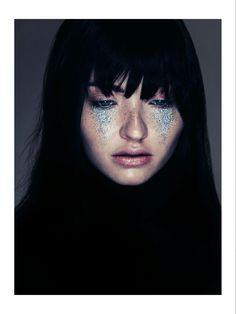 tears of glitter, black hair, pale skin, blue eyes