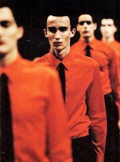 source : raf siimons I998  _  collection mode masculine minimal chemise rouge et cravate noire (men's fashion collection minimal red shirt and black tie)  (raf s.  est un grand couturier belge. en 20I2, il devient le 6e à prendre la responsabilité de la haute couture chez Dior, remplaçant Galliano. depuis 20I6 il est le directeur de la création de Calvin Klein. Il a été nommé aux Globes de Cristal en 20I5 dans la catégorie Meilleur créateur de mode.)