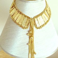 Gold Color Collar Necklace Set Gold color metal necklace. Small rectangular plates attached by small gold chains in a collar shape. Chain tassel hanging from the middle of the necklace. Matching earrings included. Makes an interesting statement piece. Jewelry Necklaces