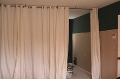 Curtain room divider DIY. These people used a Ceiling Mount Curtain Rod from Walmart and inexpensive curtains from IKEA.