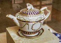 Derby porcelain teapot (with stand) painted in enamel colors and gold. Painted mark a crown and D blue enamel. 1775-1782 Norwich Castle Museum