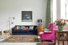 Colorful living room with pink couch & carpet with flowers