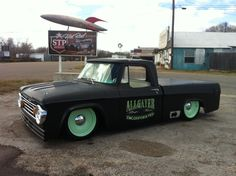 Dodge D100 sweepside pickup on sold wheels and slammed and painted in satin black and custom door graphics.