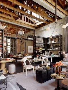 It is very industrial, but I LOVE the space, it is decorated with vintage and rustic pieces that scream farm house to me...Check out the back space, we could make our work shop similar to this, I also like the rafters for the ceiling very hay barnish