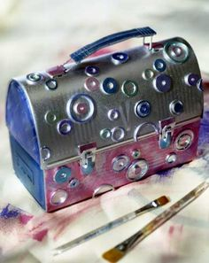 Art-Filled Caddy  An old lunch box is given new life as an art supply caddy. For texture, a variety of hardware washers were added to the surface and then highlighted with metallic paints. Mom will appreciate a new way to organize her supplies.