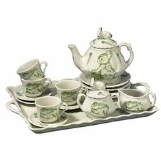 A sweet children's tea set for four is decorated with bunnies among cabbages and carrots.The green toile design and the sculpted bunnies a top the teapot and creamer adds an appealing charm to this ceramic tea service. Suitable for small hands, the set is a wonderful gift for a child's tea party.  Set includes teapot, cream and sugar set, four teacups and saucers, four dessert plates, and tray.