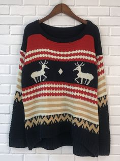 A knit sweater featuring a graphic of elk with color block stripe, long sleeves, a round neckline, and ribbed trim. Matching pants available.