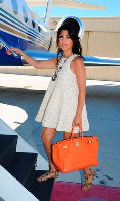 Kourtney Kardashian. White trapeze dress. Orange Hermes Birkin handbag. Leopard flat sandals.
