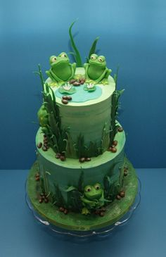 I made this froggy cake for a little boy turning 4. He loves frogs, so there is one for each year on his cake. It is vanilla cake filled and frosted with vanilla buttercream. All other decorations, including the frogs, are made from modeling chocolate.    www.facebook.com/madhousebakes