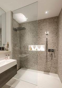 Baño en grises y blanco, donde el punto de atención son las paredes de la ducha que aportan textura.