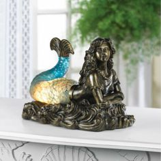 Get swept away by the alluring glow of this beautiful mermaid lamp. She rests on top of curling waves and her tail lights up with ocean-blue glow.What sailor c