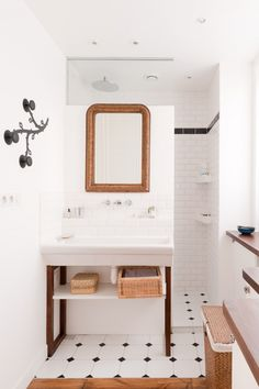 White bathroom. Like the shape of the vanity & basin top. Easy to do. Baskets. Different tiles though