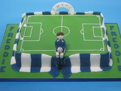 Football pitch cake made from chocolate sponge, covered in fondant and wrapped in a fondant scarf.