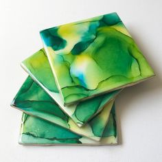 Add some colour and beauty to your home with this one-of-a-kind alcohol ink and resin ceramic coaster set. No two tiles are the same. Each tile is hand painted with alcohol inks and coated in a food safe, heat resistant epoxy. Multiple styles and colours to choose from, be sure to browse the shop for more options! What you see is what you get. The coasters shipped to you are the ones shown in this listing. Care Instructions: Coasters are not dishwasher safe Wipe coaster clean with a damp cloth D Alcohol Ink Tiles, Alcohol Ink Crafts, Alcohol Ink Painting, Alcohol Inks, Ceramic Coasters, Tile Coasters, Green Alcohol, Arts And Crafts, Diy Crafts