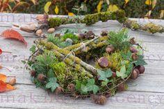 Floristische Dekorationen mit Fundstuecken aus dem Herbstwald: Waldkranz aus Moos, Zweigen, Hedera ( Efeu ), Pinus ( Kiefer ), Aesculus ( Kastanien ) und Fagus ( Bucheckern-Huellen ), Einmachglas als Windlicht in der Mitte