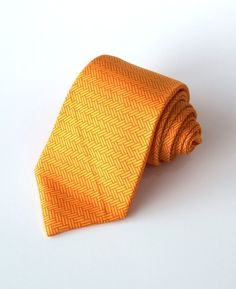ORANGE MASONRY - More than just brick laying, this tie creates interest in an otherwise monotonous job. Being a highly durable form of construction, this pattern emulates a stable and hardworking man. Set on an orange background, a very popular colour for ties
