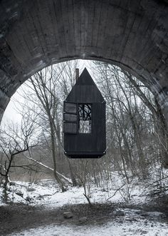 H3T architects' 'flying black house' looms beneath a bridge in the czech republic
