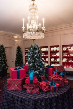 With decor designed by Carolina Herrera, the White House China Room was decorated with fresh pine, evergreen, and eucalyptus garland. The central table is wrapped in classic navy plaid and topped with a pine tree and vibrant red gift boxes. Throughout the room, Kailua Blue ribbons represent the Obama China Service.