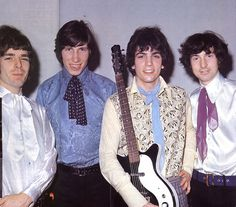 Pink Floyd looking happy in their satin and scarves.