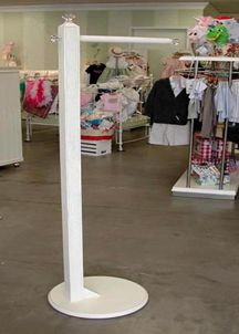 DIY Retail Store Fixtures.  I think that t-fixture would be easily made.  It's just a matter of a 4x4 post, attatched to a plywood base, and installing the metal rod pushed halfway thru and secured.  It would be a very cute idea for the child/spouse/bestie in your life who likes to pick out their clothes the night before, right?