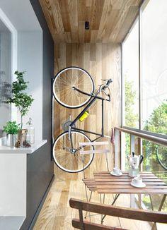 balcon vitré moderne aménagé avec des meubles en bois et un accroche vélo mural vertical