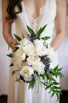 Asymmetric and Cascading ivory bouquet with green and blue accents; incorporating garden roses, peonies, lavender, privet berries and jasmine vines.Greer G. Gattuso (photographer).