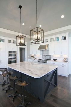 white and gray stone countertops lined with Restoration Hardware Tractor Seat Barstools atop dark floors. A row of small glass-front cabinets are stacked over white shaker cabinets paired with white and grey stone countertops and matching backsplash.
