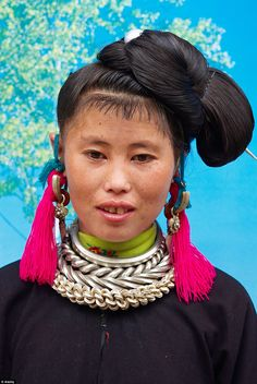 A woman from the Black Miao ethnic group, in Guizhou Province, China. Its female members adorn themselves in neon colours and  jewels