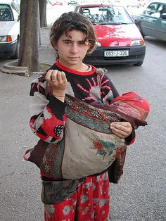 Très jeune femme gitane tenant contre sa poitrine un bébé niché dans une large écharpe passée sur son épaule, en guise de «sac» ~~~~ Very young gypsy woman holding a baby nested in a large scar wrapped over her shoulder.
