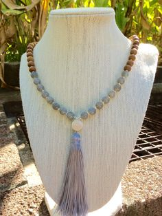 "Earthy sandalwood beads contrast beautifully with ethereal moonstones in this 108 bead mala. The mala is finished with a soft grey tassel made from fine Chinese knotting cord. I love working with this material because it doesnt fray. I also used a pretty ceramic focal bead with soothing concentric rings that accent the moonstones glow. A stone for ""new beginnings"", Moonstone is believed to be a stone of inner growth and strength. It can soothe stress and help restore feelings of calm…"