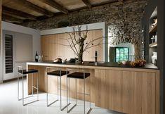 reforma cocina abierta y moderna en casa rural rehabilitada con isla y módulos adicionales, paredes de piedra, techos con vigas vistas de madera, suelo resina epoxi. presupuestON.com
