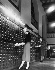 """""""Library catalogue files are checked by (left to right) Dorothy Gnoerrendale, 7711 Euclid Ave.; Mary Mason, 13318 Cedar Rd., Cleveland Heights, and Delores Hammons, 10017 Parkgate Ave"""" — photo verso."""