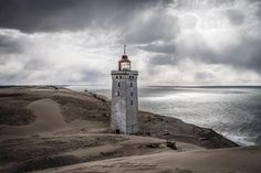 [ this location is one of my favorites on the Danish west coast. I remember the weather was awfully with a very strong offshore wind and dark clouds.  Rubjerg Fyr (lighthouse) will probably collapse into the sea in about 10 years. The sea is patiently eroding the area from the west. On average it is about a few meters per year with remaining 20-30 meters between pine and the sea you can quickly find that the lighthouse will probably disappear in the 2020's.  Such a dramatic fate could not…