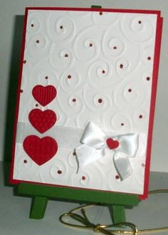 darling Valentine card: embossed card front, red jewels, trio of red hearts and sweet satin ribbon and bow.